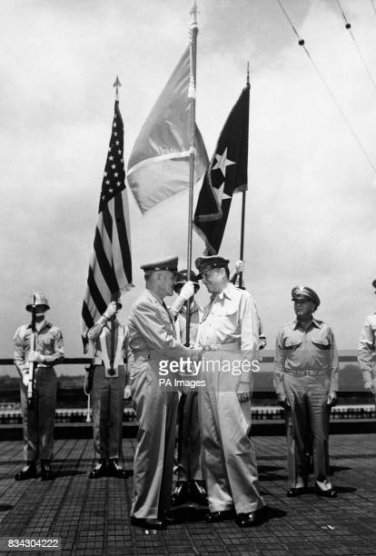 General JLawton Collins chief of staff United states Army shaking the hand of General of the Army Douglas MacArthur commanderinchief of the United...