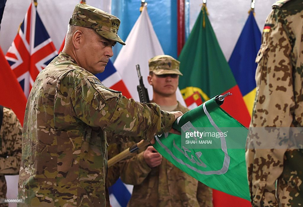 US General John Campbell rolls the flag of the NATOled International Security Assistance Force during a ceremony marking the end of ISAF's combat...