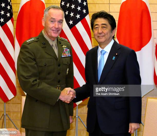 General Joseph Dunford chairman of the US Joint Chiefs of Staff and Japanese Prime Minister Shinzo Abe shake hands during their meeting at Abe's...