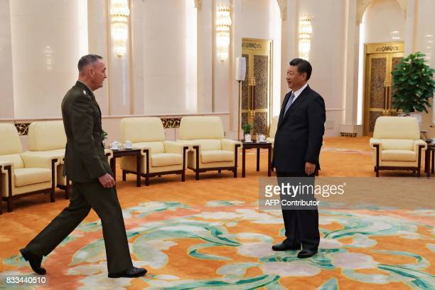 General Joseph Dunford the chairman of the US joint chiefs of staff walks to shake hands with China's President Xi Jinping at the Great Hall of the...