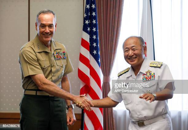 General Joseph Dunford the chairman of the US Joint Chiefs of Staff shakes hands with Japan's Chief of Staff of Joint Staff Katsutoshi Kawano at the...