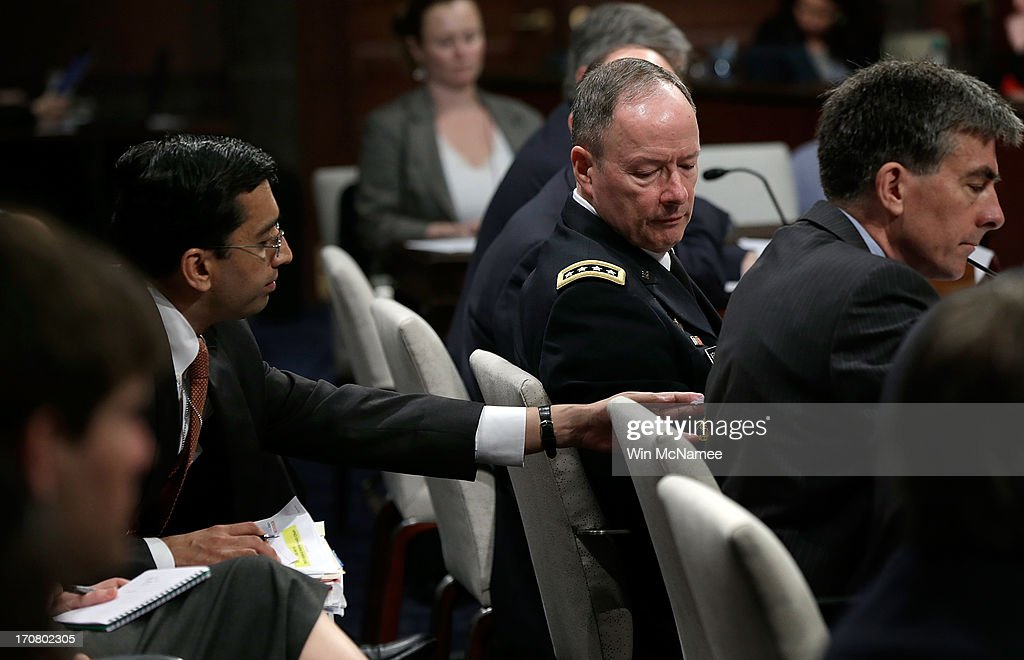 General Keith Alexander, Director of the National Security Agency, receives a note from an aide while testifying before the House Select Intelligence Committee June 18, 2013 in Washington, DC. The committee heard testimony on the topic of 'how the disclosed NSA programs protect Americans from terror attacks on US soil, and why the disclosure of that classified information aids our adversaries.'