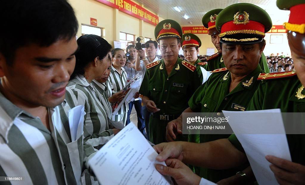 General Le Quy Vuong (C), Vice Minister of Public Security and police officers hand over amnesty certificates to prisoners at the Hoang Tien prison in Chi Linh district, northern province of Hai Duong on August 30, 2013. Vietnam will free more than 15,000 convicts to mark its independence day celebrations, the president's office said on August 29, in a major amnesty that excludes prominent political prisoners. AFP PHOTO/HOANG DINH Nam