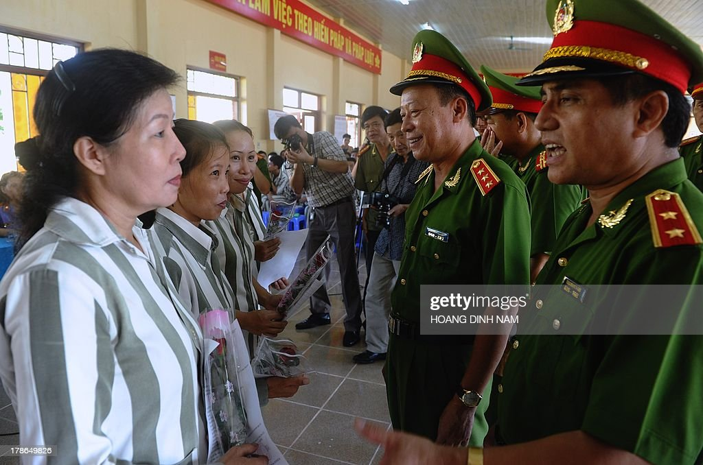 General Le Quy Vuong (C), Vice Minister of Public Security and police officers talk with female prisoners after handing them amnesty certificates during a ceremony at the Hoang Tien prison in Chi Linh district, northern province of Hai Duong on August 30, 2013. Vietnam will free more than 15,000 convicts to mark its independence day celebrations, the president's office said on August 29, in a major amnesty that excludes prominent political prisoners. AFP PHOTO/HOANG DINH Nam