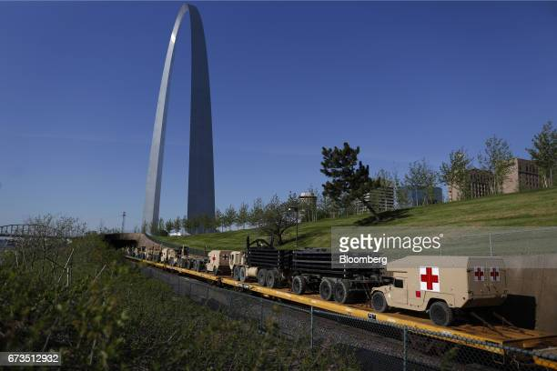 AM General LLC High Mobility Multipurpose Wheeled Vehicle ambulances sit on a US Army equipment train passing by the Gateway Arch in St Louis...