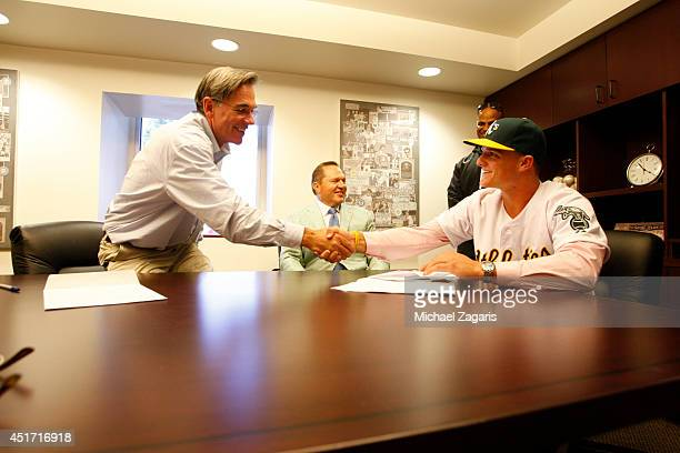 General Manager Billy Beane of the Oakland Athletics shakes hands with Athletics first round draft pick Matt Chapman after getting Chapman's contact...