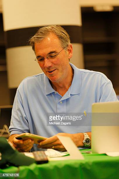 General Manager Billy Beane of the Oakland Athletics sits in the Athletics draft room during the first day of the 2015 MLB Draft at Oco Coliseum on...