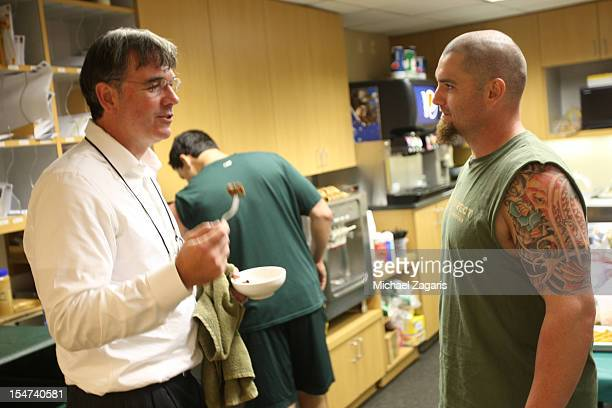 General Manager Billy Beane of the Oakland Athletics talks with Jonny Gomes in the clubhouse prior to the game against the Detroit Tigers at the...