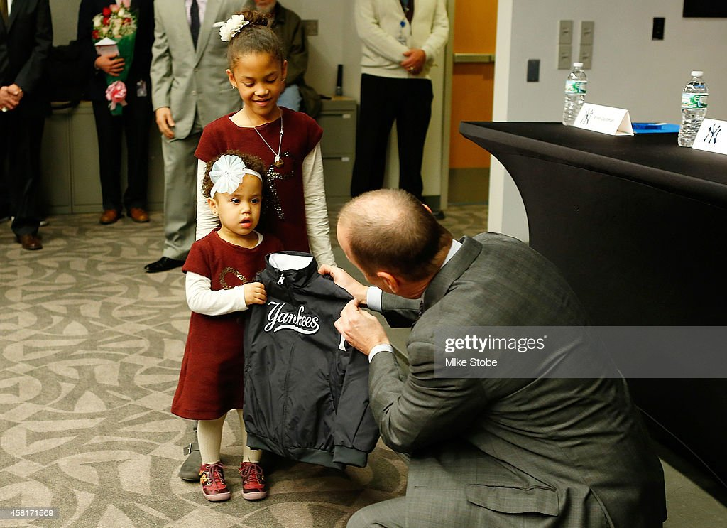 General Manager Brian Cashman presents Carlos Beltran's daughter Ivana and Kiara with Yankee jackets during Beltran's introductory press conference at Yankee Stadium on December 20, 2013 in the Bronx borough of New York City.