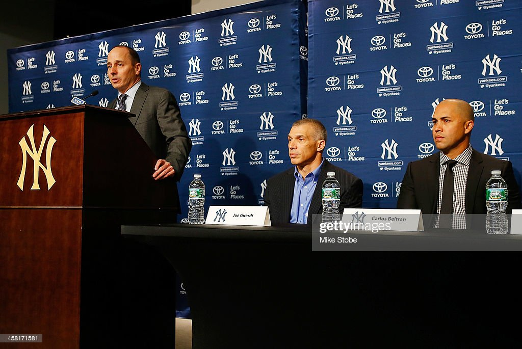 General Manager Brian Cashman speaks to the as manager Joe Girardi and Carlos Beltran look on during Beltran's introductory press conference at Yankee Stadium on December 20, 2013 in the Bronx borough of New York City.