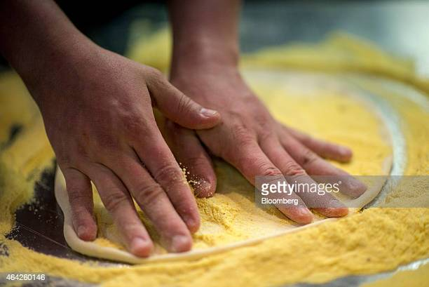 General Manager Erick Orellana stretches pizza dough at a Domino's Pizza Inc 'pizza theater' location in Jersey City New Jersey US on Friday Feb 20...