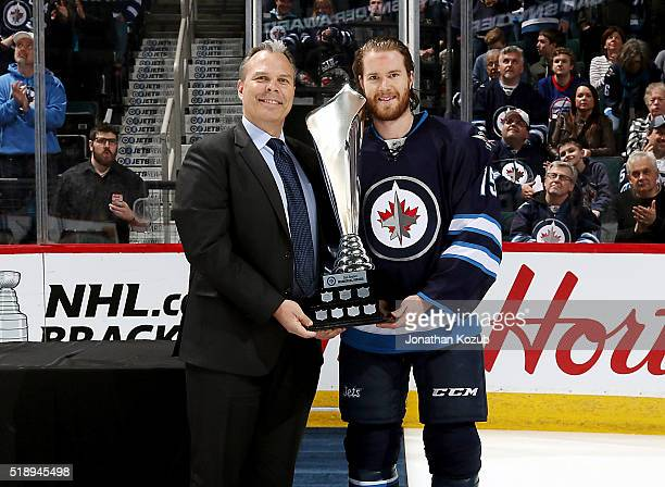 General Manager Kevin Cheveldayoff of the Winnipeg Jets presents Matt Halischuk with the Dan Snyder Memorial Award prior to NHL action against the...