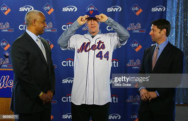 General Manager Omar Minaya watches Jason Bay and put on a New York Mets hat as Mets COO Jeff Wilpon looks on during a press conference to announce...