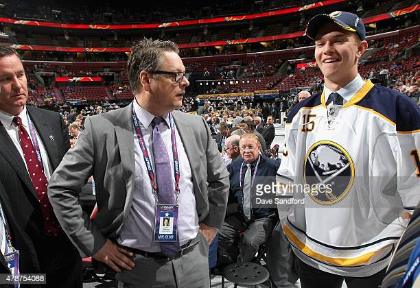 General Manager Tim Murray of the Buffalo Sabres and 51st overall pick Brendan Guhle look on from the draft floor during the 2015 NHL Draft at BBT...