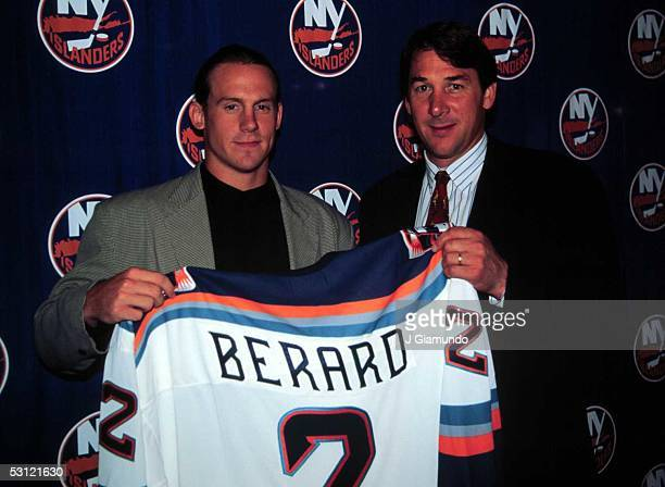 General managers Mike Milbury looks on as Bryan Berard signs his contract to play for the New York Islanders circa 1996 at the Nassau Coliseum in...