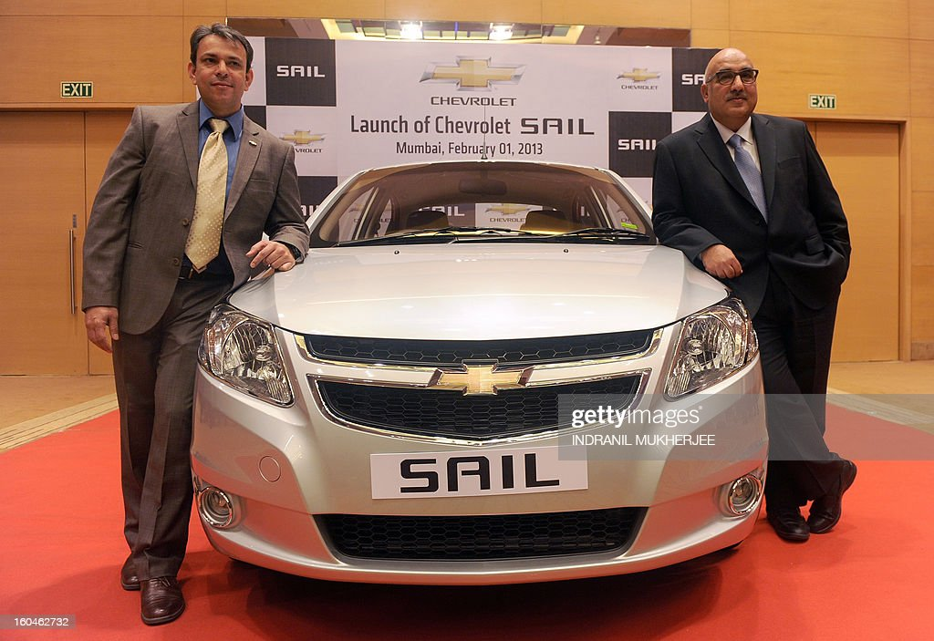 General Motor personell Yudhvir Singh (L) and Anil Mehrotra pose with the new Chevrolet Sail sedan motor-car during the launch in Mumbai on February 1, 2013. Sail, the latest sedan from General Motors, is available in four different variants of petrol and diesel. AFP PHOTO/Indranil MUKHERJEE