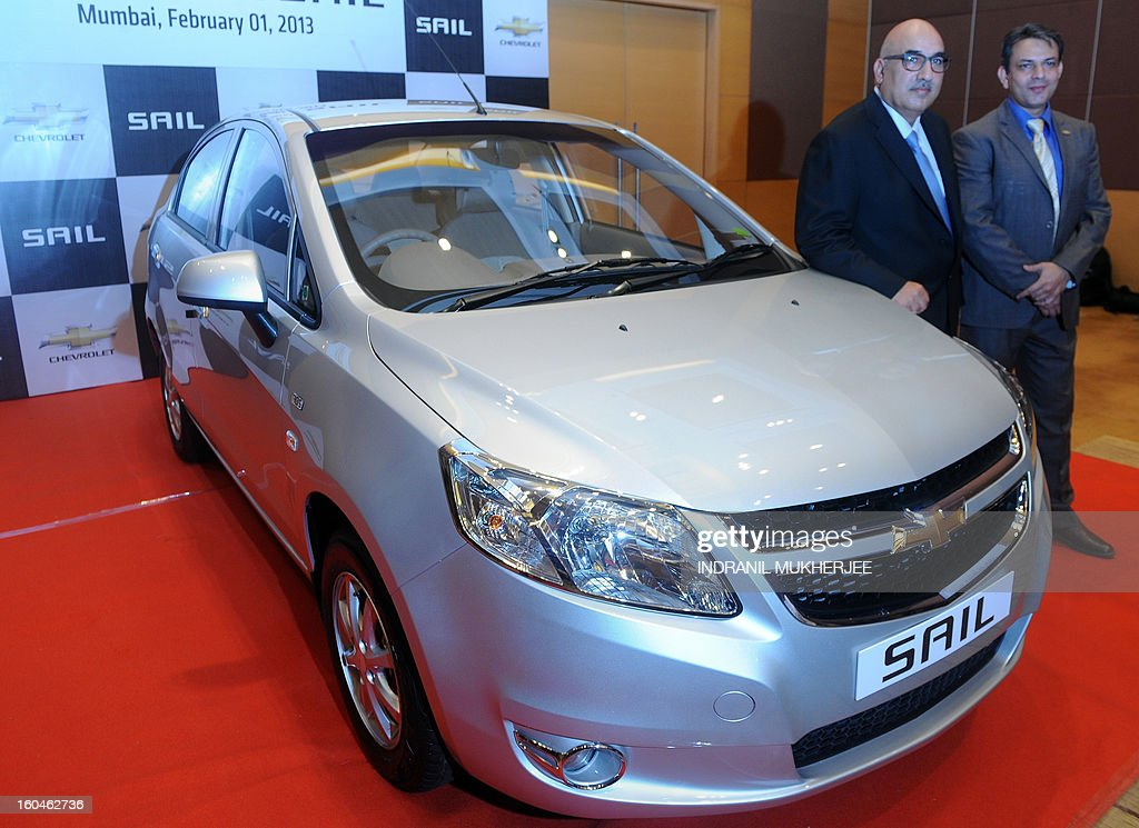 General Motor personell Yudhvir Singh (R) and Anil Mehrotra pose with the new Chevrolet Sail sedan motor-car during the launch in Mumbai on February 1, 2013. Sail, the latest sedan from General Motors, is available in four different variants of petrol and diesel. AFP PHOTO/Indranil MUKHERJEE