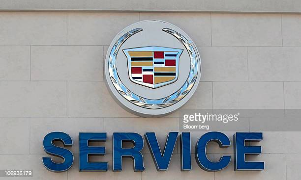 A General Motors Co Cadillac logo hangs outside the service area for the Les Stanford General Motors dealerships in Dearborn Michigan US on Wednesday...