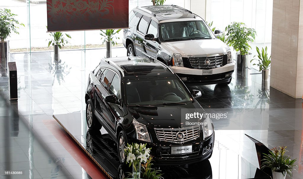 General Motors Co. Cadillac SRX, left, and Escalade Hybrid sports utility vehicle (SUV) are displayed at a dealership in Shanghai, China, on Friday, Feb. 8, 2013. China's services industries grew at the fastest pace since August as gains in retailing and construction aid government efforts to drive a recovery in the world's second-biggest economy. Photographer: Tomohiro Ohsumi/Bloomberg via Getty Images