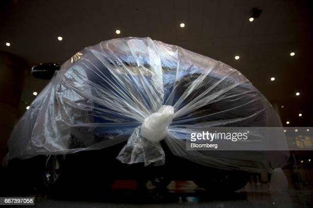 A General Motors Co Chevrolet brand Bolt electric vehicle sits under plastic ahead of the 2017 New York International Auto Show in New York US on...