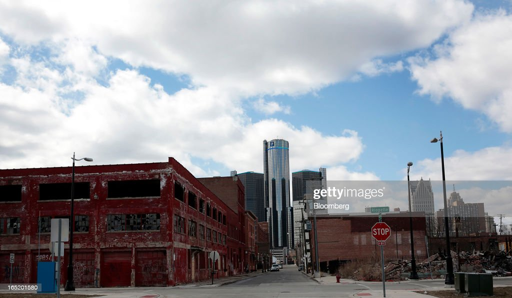 General Motors Co. (GM) headquarters is seen in the distance past a run down building in Detroit, Michigan, U.S., on Monday, April 1, 2013. U.S. automakers are surging, while Detroit is in such distress that it's being taken over by the state of Michigan today. Photographer: Jeff Kowalsky/Bloomberg via Getty Images