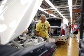 General Motors' worker assembles a 2013 Cadillac ATS on the assembly line at the General Motors Lansing Grand River Assembly Plant July 26 2012 in...