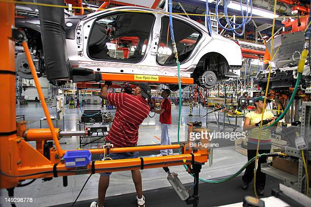 General Motors' workers assemble a 2013 Cadillac ATS on the assembly line at the General Motors Lansing Grand River Assembly Plant July 26 2012 in...