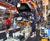 General Motors workers assemble a 2013 Cadillac ATS on the assembly line at the General Motors Lansing Grand River Assembly Plant July 26 2012 in...