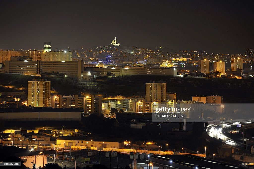 General night view taken on January 3, 2013 shows residential buildings (foreground) located in the northern districts in the French southern city of Marseille, one week ahead of the 2013 'Marseille-Provence European Capital of Culture' event. In the background, at center, is seen the Notre-Dame de la Garde basilica. AFP PHOTO/GERARD JULIEN