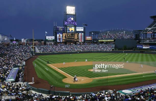 A general overall view as Chad Moeller of the Milwaukee Brewers fouls a ball back against Shawn Estes of the Colorado Rockies as storm clouds loom in...