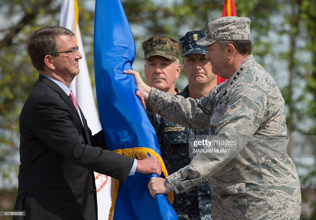US General Philip Breedlove (R) hands over the command flag to US Defence Secretary Ashton Carter (L) as US General Joseph Dunford (2nd L) and Command Master Chief Crispian Addington look on during a ceremony on May 3, 2016 at the Patch Barracks in Stuttgart, southern Germany. The ceremony took place at the barracks as US General Curtis Scaparrotti was introduced as Commander of the US European Command, taking over from US General Philip Breedlove. / AFP / dpa / Marijan Murat / Germany OUT