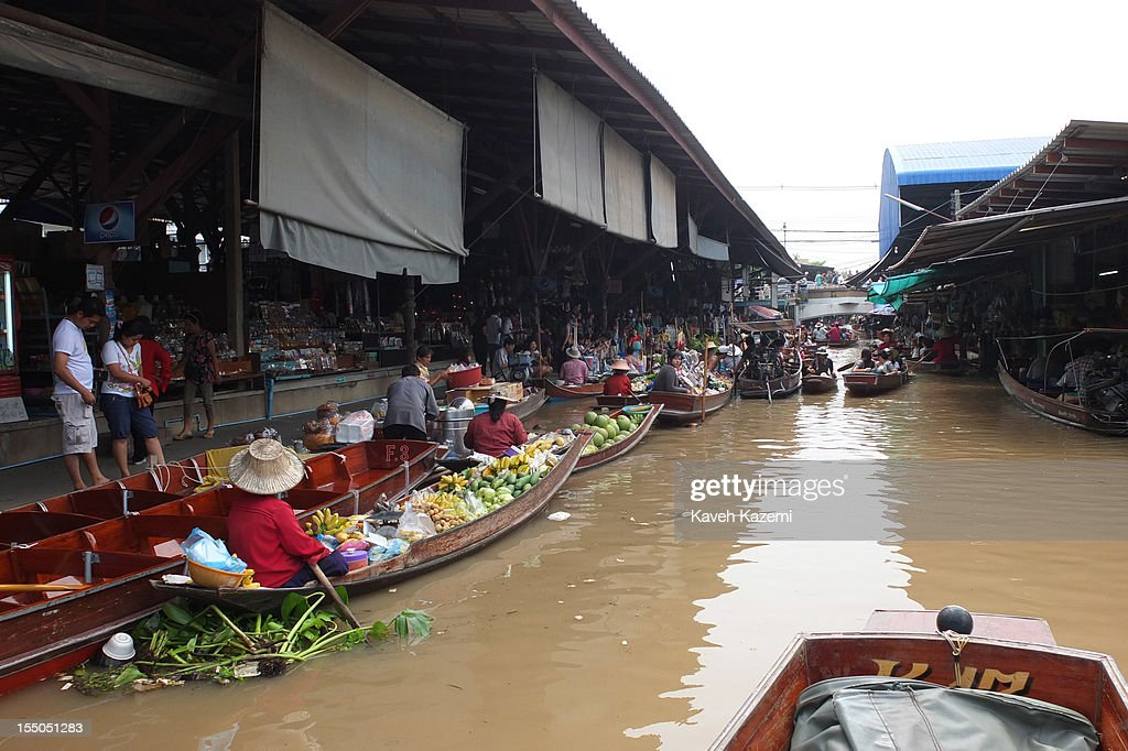 A general scene of the floating market with tourists and Thai vendors on their boats circulating in the canal in on October 14 in Damnoen Saduak, Thailand. Damnoen Saduak is a district in the province of Ratchaburi in central Thailand. The central town has become a tourist attraction with its famous floating market.