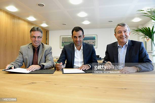 General secretary Helmut Sandrock of the German Football Federation DFB Robin Dutt and DFB President Wolfgang Niersbach sign the contrect prior to...
