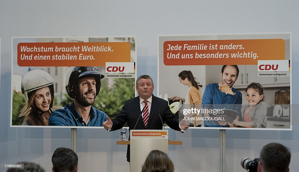 CDU General Secretary Hermann Groehe addresses a press conference during the unveiling of the election campaign placards of the Christian Democratic Party at their headquarters in Berlin, Germany on August 5, 2013. Germany goes to the polls in parliamentary elections on September 22, 2013. Slogans (R-L) read 'Growth needs vision. And a solid Euro' and 'Every family is different. Und you are especially important to us'. AFP PHOTO / JOHN MACDOUGALL