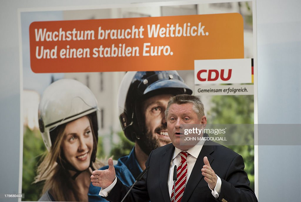 CDU General Secretary Hermann Groehe addresses a press conference during the unveiling of the election campaign placards of the Christian Democratic Party at their headquarters in Berlin, Germany on August 5, 2013. Germany goes to the polls in parliamentary elections on September 22, 2013. Slogan on placard reads 'Growth needs vision. And a solid Euro' .