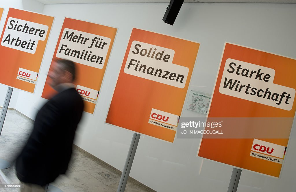 CDU General Secretary Hermann Groehe arrives for a press conference for the unveiling of the election campaign placards of the Christian Democratic Party at their headquarters in Berlin, Germany on August 5, 2013. Germany goes to the polls in parliamentary elections on September 22, 2013. Slogan on placard reads (L-R) 'Strong Economy', 'Sturdy Finances', 'More for Families', 'Job Security'.