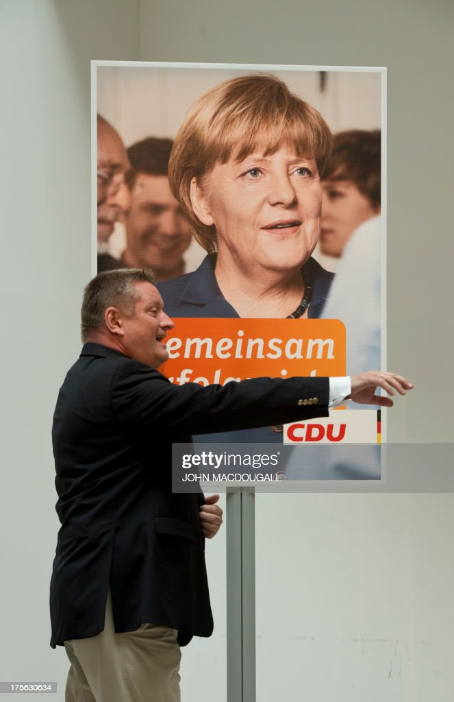 CDU General Secretary Hermann Groehe gestures as he stands in front of a picture of Angela Merkel during a press conference for the unveiling of the election campaign placards of the Christian Democratic Party at their headquarters in Berlin, Germany on August 5, 2013. Germany goes to the polls in parliamentary elections on September 22, 2013. Slogan on placard reads 'Every family is different.And you are especially important to us'.