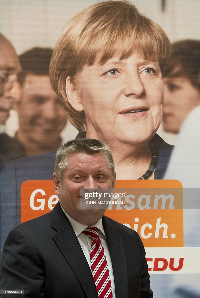 CDU General Secretary Hermann Groehe reacts as he stands in front of a picture of Angela Merkel during a press conference for the unveiling of the election campaign placards of the Christian Democratic Party at their headquarters in Berlin, Germany on August 5, 2013. Germany goes to the polls in parliamentary elections on September 22, 2013. AFP PHOTO / JOHN MACDOUGALL