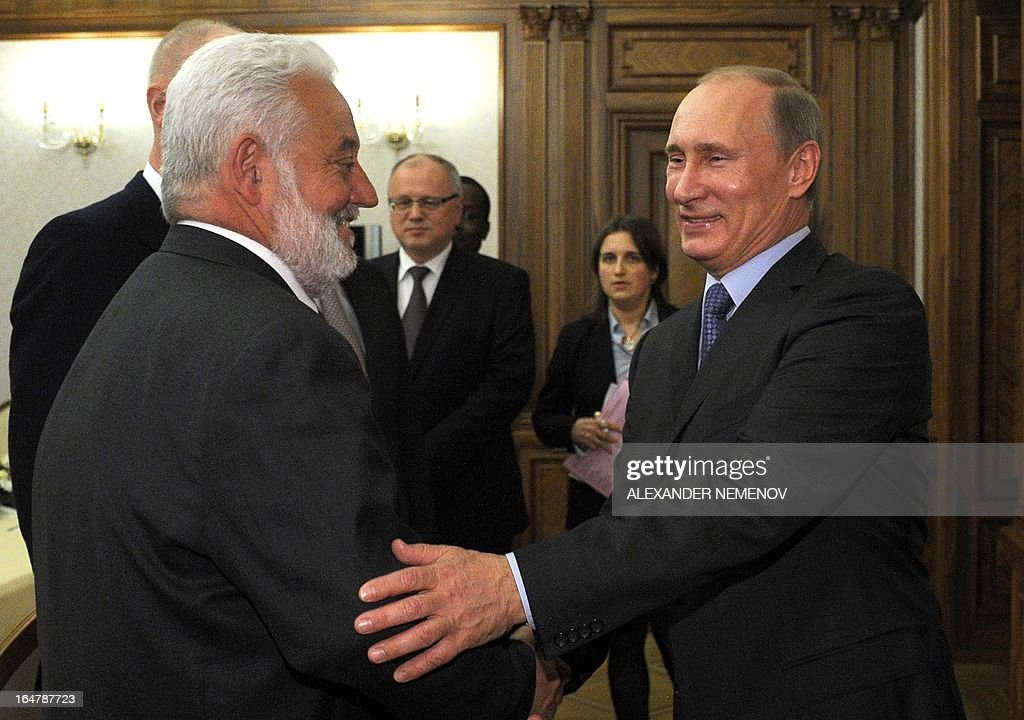 General Secretary of the Bureau of International Expositions (BIE) Vicente Gonzalez Loscertales (L) shakes hands with Russian President Vladimir Putin during their meeting in Sochi on March 28, 2013, as Russia's city of Yekaterinburg will host for World Expo 2020.