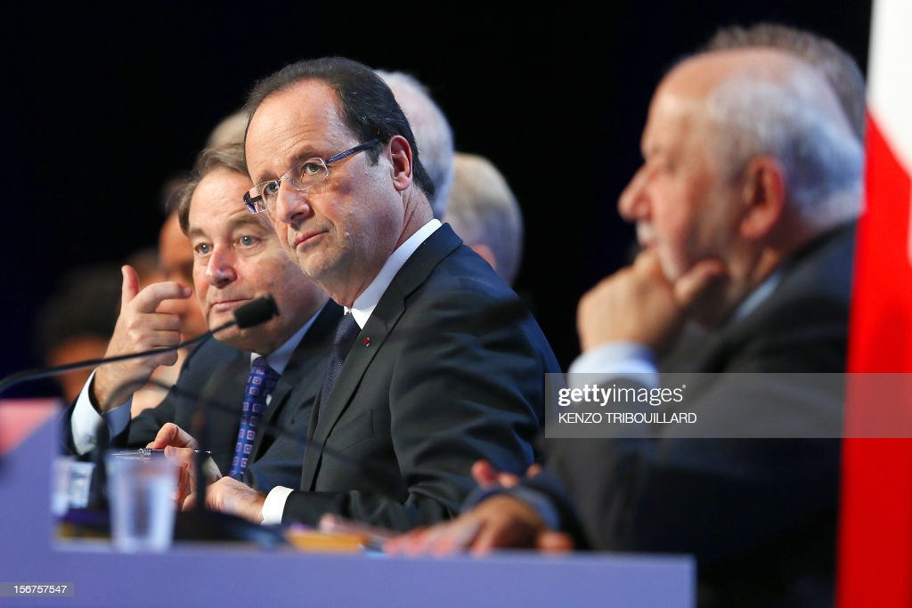General Secretary of the French Mayors Association (AMF) Andre Laignel (L) speaks as French President Francois Hollande (C) and first vice-President of the AMF, Andre Rossinot, listen during the opening ceremony of the 95th French Mayors congress, on November 20, 2012 in Paris.