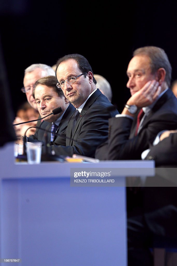 General Secretary of the French Mayors Association (AMF) Andre Laignel, French President Francois Hollande and Paris Mayor Bertrand Delanoe listen to the speeches during the opening ceremony of the 95th French Mayors congress, on November 20, 2012 in Paris. AFP PHOTO KENZO TRIBOUILLARD