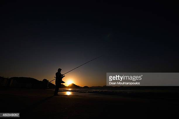 A general view as a local man fishes on the Copacabana Beach as the sun rises prior to the 2014 FIFA World Cup on June 9 2014 in Rio de Janeiro Brazil