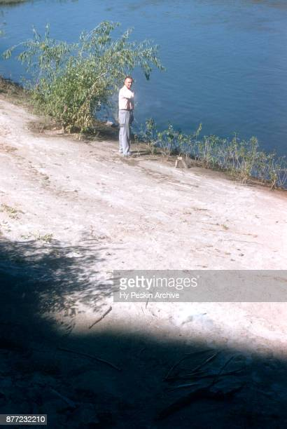 General view as a man shoots a bottle as he takes a break from woodchuck hunting in the wilderness circa July 1951 in Lewiston Idaho