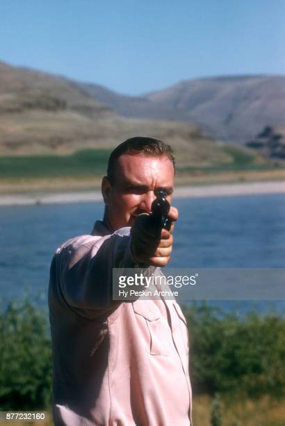 General view as a man shows off his gun as he takes a break from woodchuck hunting in the wilderness circa July 1951 in Lewiston Idaho