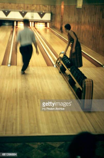 General view as a man throws his ball and a woman grabs her ball from the ball return during a game in a bowling alley circa 1955