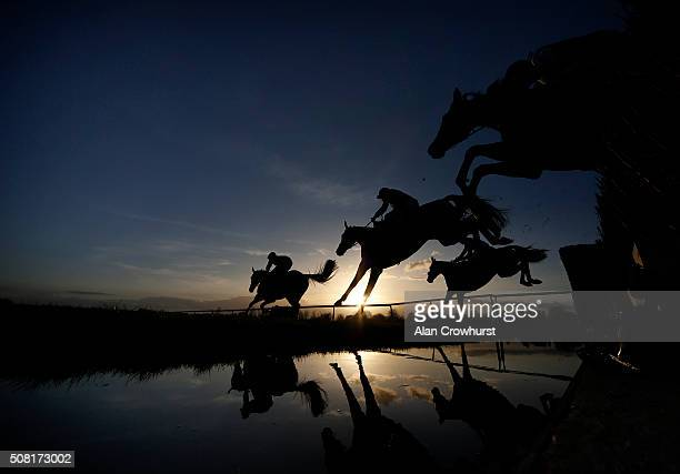 A general view as a runners clear the water jump in The Running Hare Handicap Steeple Chase as the sun begins to set at Leicester racecourse on...