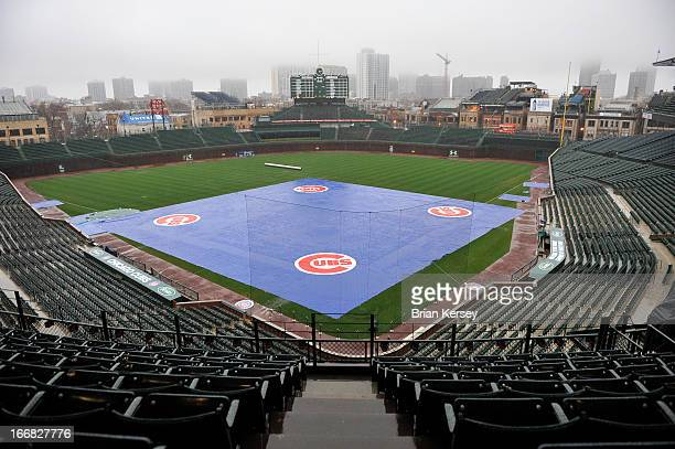 General view as a tarp covers the infield as a heavy rain falls at Wrigley Field on April 17 2013 in Chicago Illinois The game between the Chicago...