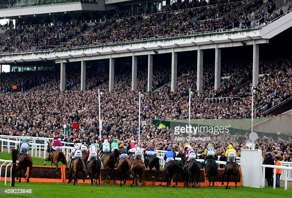A general view as runners clear a flight of hurdles in front of the grandstands at Cheltenham racecourse on November 15 2014 in Cheltenham England