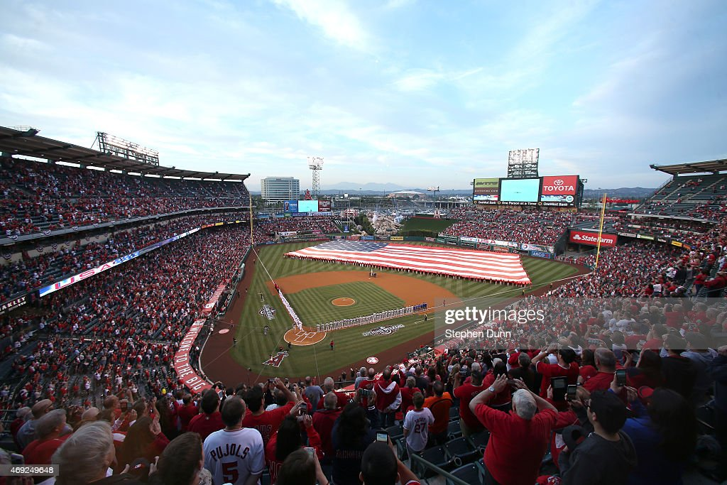 General view as the Kansas City Royals and the Los Angeles Angels of Anaheim line the field with a giant American flag during the national anthem for...