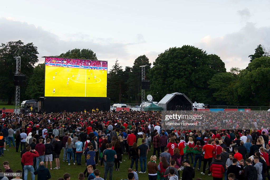 A general view as Welsh football fans watch the Wales v Belgium Euro 2016 quarter-final match on a big screen at the Cardiff fan zone in Coopers Field on July 1, 2016 in Cardiff, Wales.